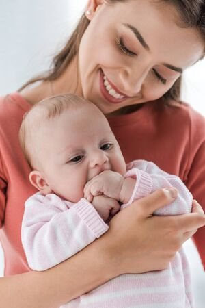 cheerful mother holding in arms adorable infant daughter at home Imagens