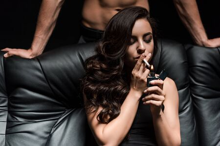 young couple sitting on sofa in dark room, while seductive woman smoking cigarette