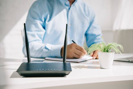 cropped view of businessman writing in notebook near router and flowerpot