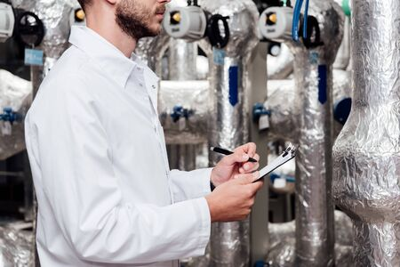 cropped view of bearded engineer in white coat holding clipboard and pen near air compressed system