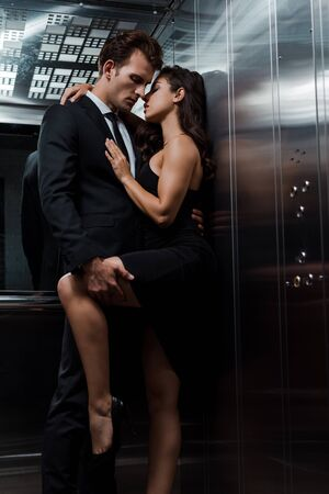 young seductive couple hugging and flirting in lift