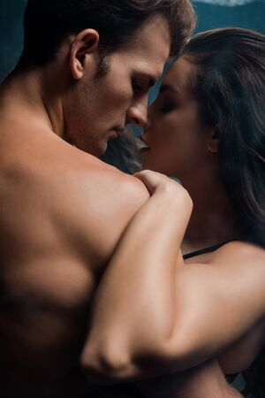 beautiful passionate couple hugging in black room with smoke