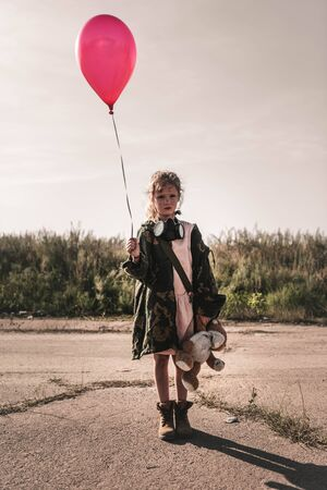 cute kid with gas mask holding red balloon, post apocalyptic concept