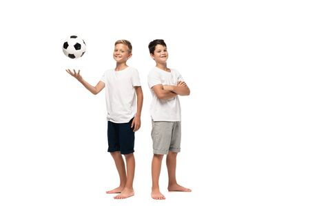 cheerful boy playing soccer ball near smiling brother standing with crossed arms on white background