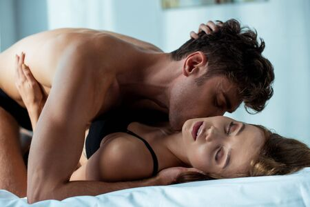 seductive man kissing passionate woman in bedroom Stockfoto