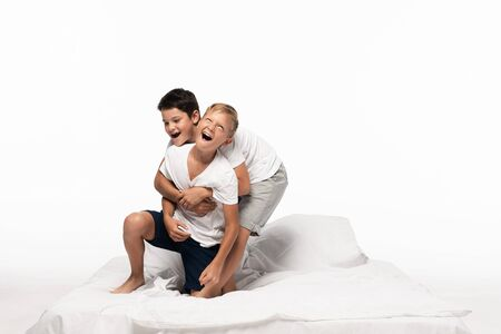 cheerful boys imitating fighting while having fun on bed isolated on white