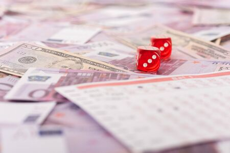 selective focus of dice near betting list on euro and dollar banknotes, sports betting concept
