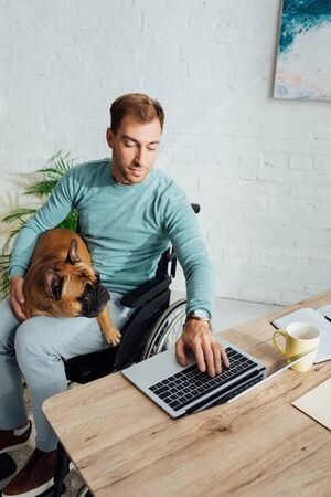 Disabled man holding french bulldog and working on laptop at home