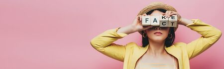 panoramic shot of asian woman holding wooden cubes in front of face with fake and fact lettering isolated on pink Stock Photo