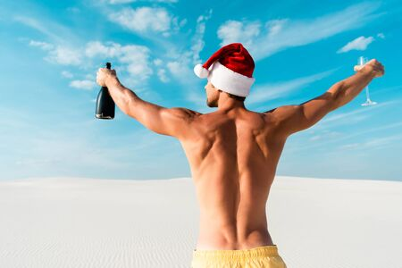 back view of sexy man in santa hat holding glass and bottle on beach in Maldives Standard-Bild