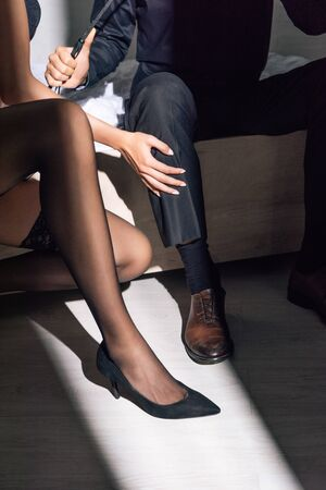 cropped view of woman in black stockings and man with flogging whip Stock Photo