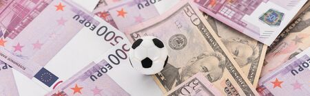panoramic shot of toy soccer ball on dollar and euro banknotes, sports betting concept