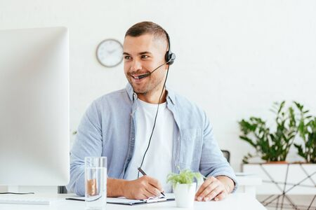 cheerful broker in headset looking at computer monitor and holding pen Imagens