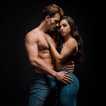 young sensual couple hugging, isolated on black