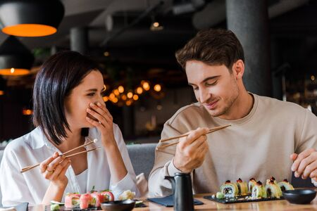 happy man holding chopsticks near cheerful woman laughing while covering face in restaurant