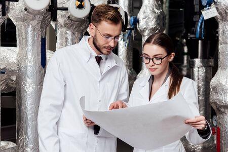 ingegneri con gli occhiali che guardano il progetto vicino al sistema del compressore d'aria