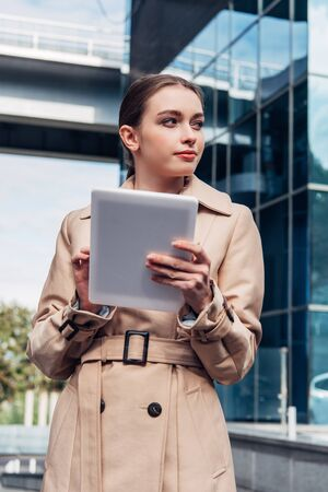 attractive woman in trench coat holding digital tablet