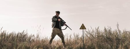 panoramic shot of handsome man holding gun near toxic symbol in field, post apocalyptic concept