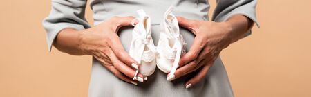 panoramic shot of pregnant woman holding shoes isolated on beige