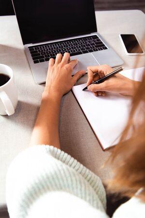 vista ritagliata della donna che scrive nel blocco note nella caffetteria con tazza di caffè, smartphone e laptop Archivio Fotografico