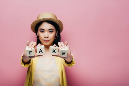 selective focus of asian woman holding wooden cubes with fake and fact lettering isolated on pink