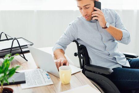 Mann im Rollstuhl, der auf Smartphone spricht und Laptop-Tastatur am Schreibtisch benutzt
