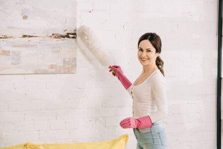cheerful housewife smiling at camera while cleaning picture on wall with dusting brush