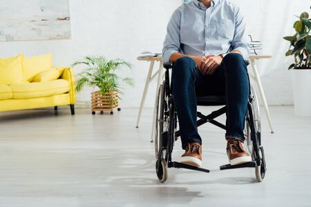 Cropped view of man sitting in wheelchair in living room