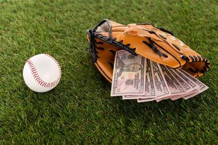 dollar banknotes in baseball glove near ball on green grass, sports betting concept Banque d'images