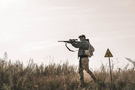 handsome man holding gun near toxic symbol in field, post apocalyptic concept Banco de Imagens