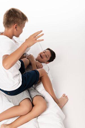 Vista aérea del niño sentado en el hermano riendo mientras se divierte en la cama sobre fondo blanco.