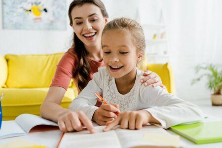 El enfoque selectivo de la niñera feliz y niño alegre apuntando con los dedos en el libro Foto de archivo