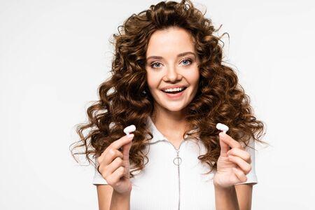beautiful smiling girl holding wireless earphones, isolated on white Foto de archivo