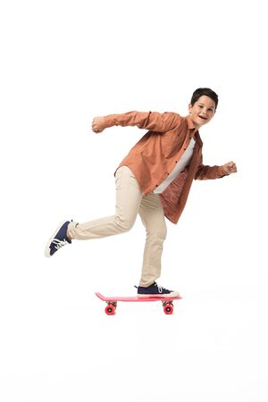 cheerful boy riding penny board while looking at camera on white background Фото со стока
