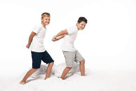 two cheerful brothers imitating bodybuilders while standing on bed isolated on white