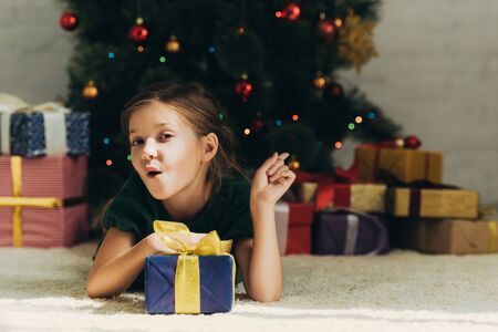 amused child pointing with finger at gift boxes while lying on floor near christmas tree