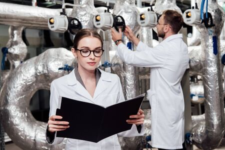 selective focus of attractive engineer in white coat looking at folder near coworker and compressed air system Archivio Fotografico