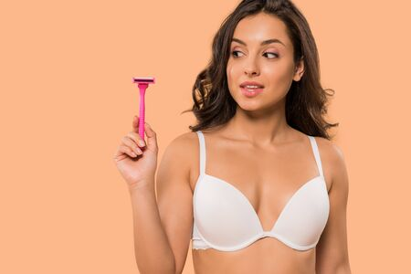 attractive woman holding pink shaving razor isolated on beige Reklamní fotografie