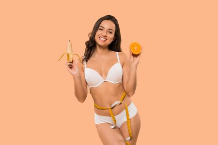 cheerful woman holding banana and orange isolated on beige