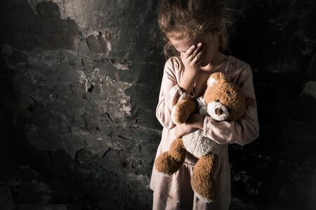 upset kid touching face while holding teddy bear in dirty room, post apocalyptic concept