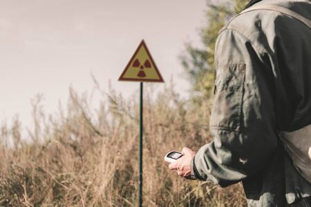 cropped view of man holding radiometer near toxic symbol, post apocalyptic concept