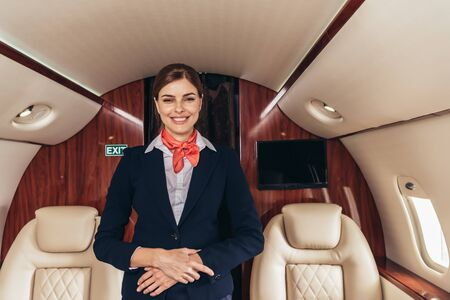 smiling flight attendant in uniform looking at camera in private plane