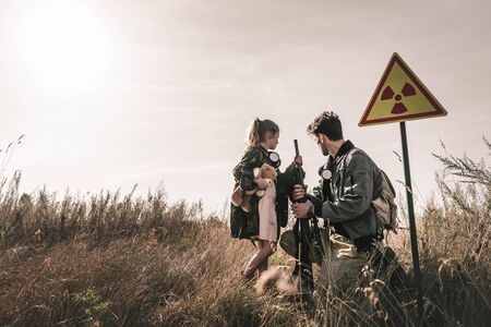 handsome man with gun near kid with teddy bear and toxic symbol, post apocalyptic concept Banco de Imagens