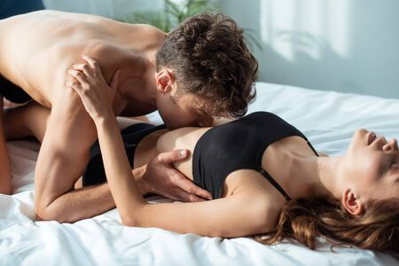 seductive man kissing passionate girlfriend in bedroom