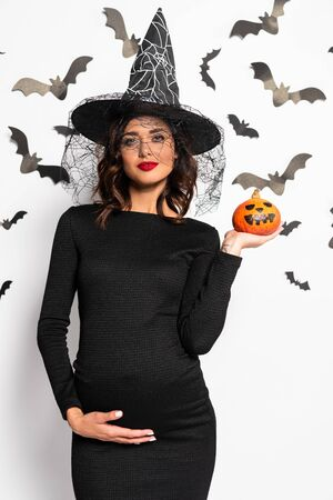 pregnant woman in witch hat holding pumpkin in Halloween