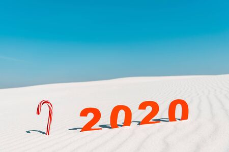2020 numbers and candy cane on white sand on beach in Maldives