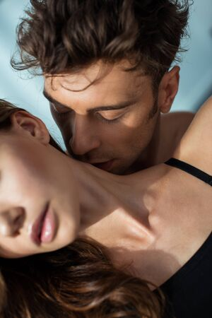 selective focus of passionate man kissing neck of girlfriend
