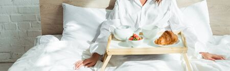 panoramic shot of woman in white shirt having breakfast in bed at morning
