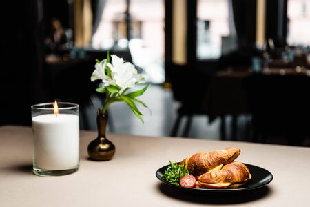 plate with croissants for breakfast on table with candle and flowers in restaurant