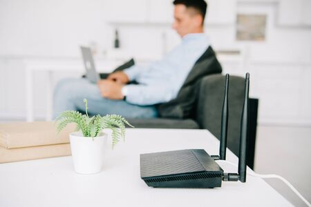 selective focus of black router on white desk near flowerpot and businessman using laptop